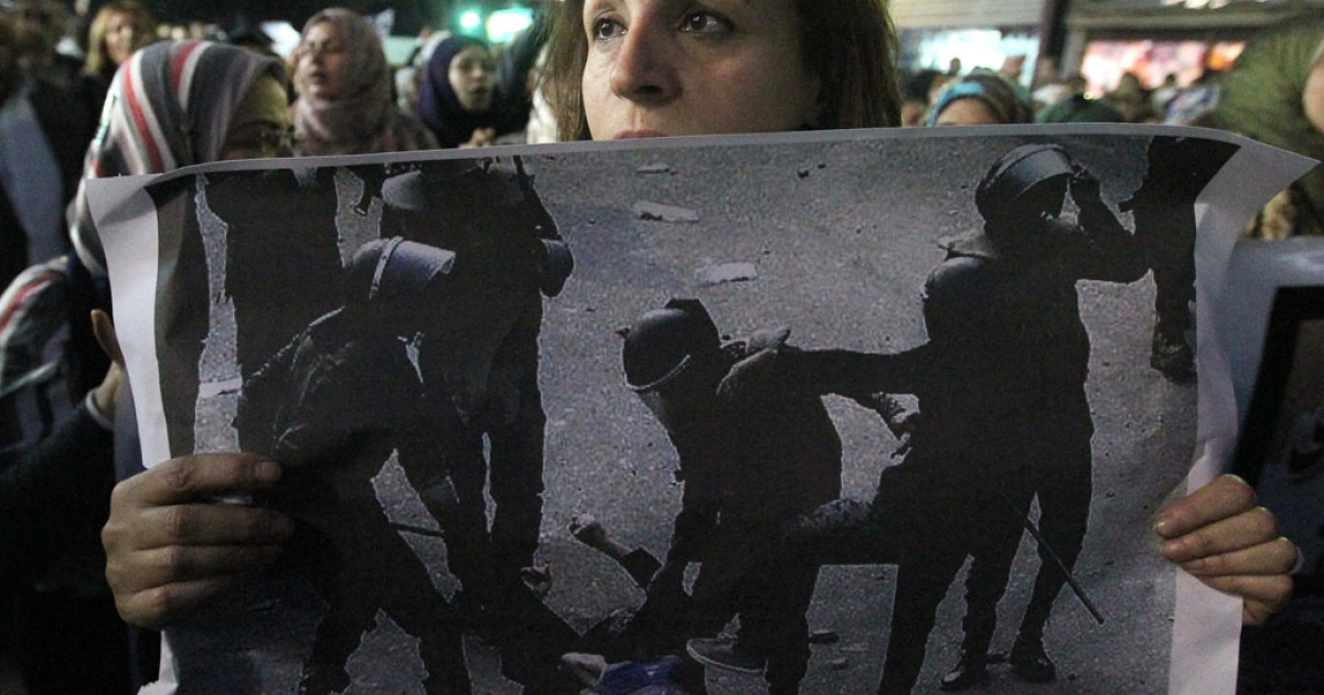 An Egyptian woman holds the widespread picture of a woman who was stripped and beaten by riot police during clashes last week as Egyptians gather for a protest in downtown Cairo to denounce the military's attacks on women and to call for an immediate end to the violence against protesters on December 20, 2011.</p>