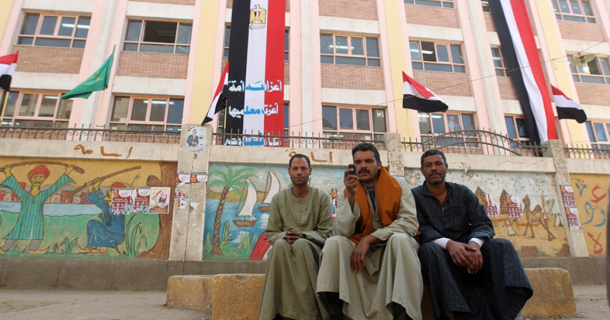Egyptians men sit outside a polling station in Minya, some 350 kms south of Cairo, during the third and final round of landmark parliamentary elections on January 3, 2012.</p>