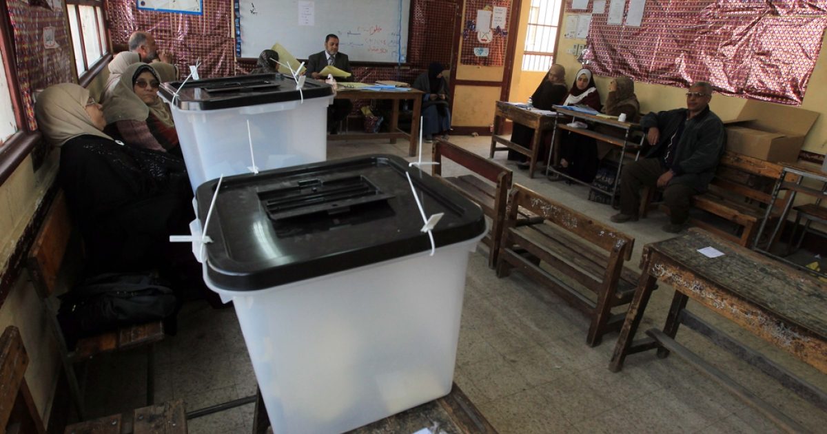 Egyptian electoral officials wait for voters at an empty polling station in Cairo during the first stage of voting for Egypt's upper house of parliament, the Shura Council. Polling got under way with only a handful of voters at several stations.</p>