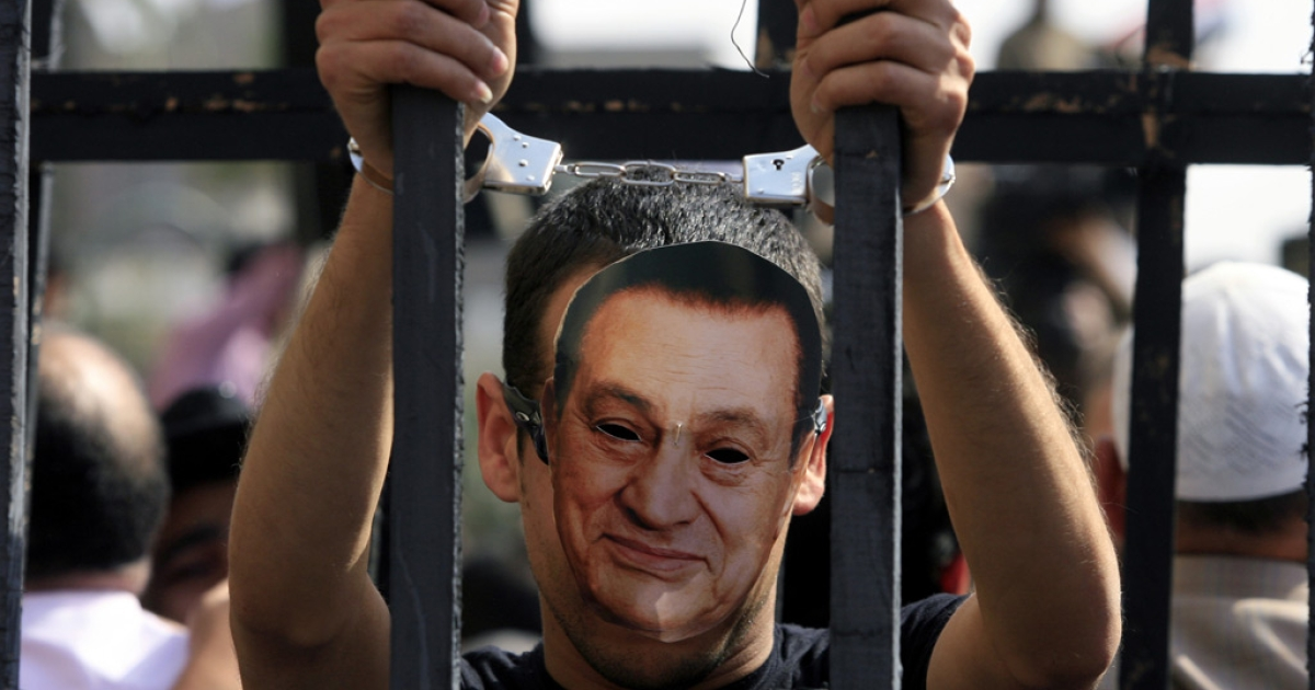 An Egyptian protester wearing the mask of ousted Egyptian president Hosni Mubarak stands with handcuffs inside a makeshift prison cell at Cairo's Tahrir Square on April 8, 2011 during a demonstration attended by tens of thousands of Egyptians.</p>