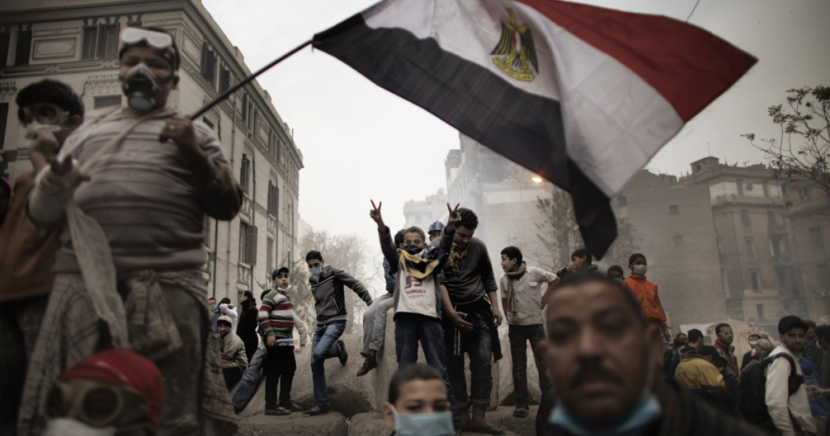 Egyptian demonstrators gathered next to a concrete block barricade during confrontations outside Cairo's security headquarters on February 6, 2012, as clashes continued in the Egyptian capital amid calls by activists for civil disobedience in Egypt. Egypt will put 16 Americans and 27 other pro-democracy activists on trial on February 26.</p>