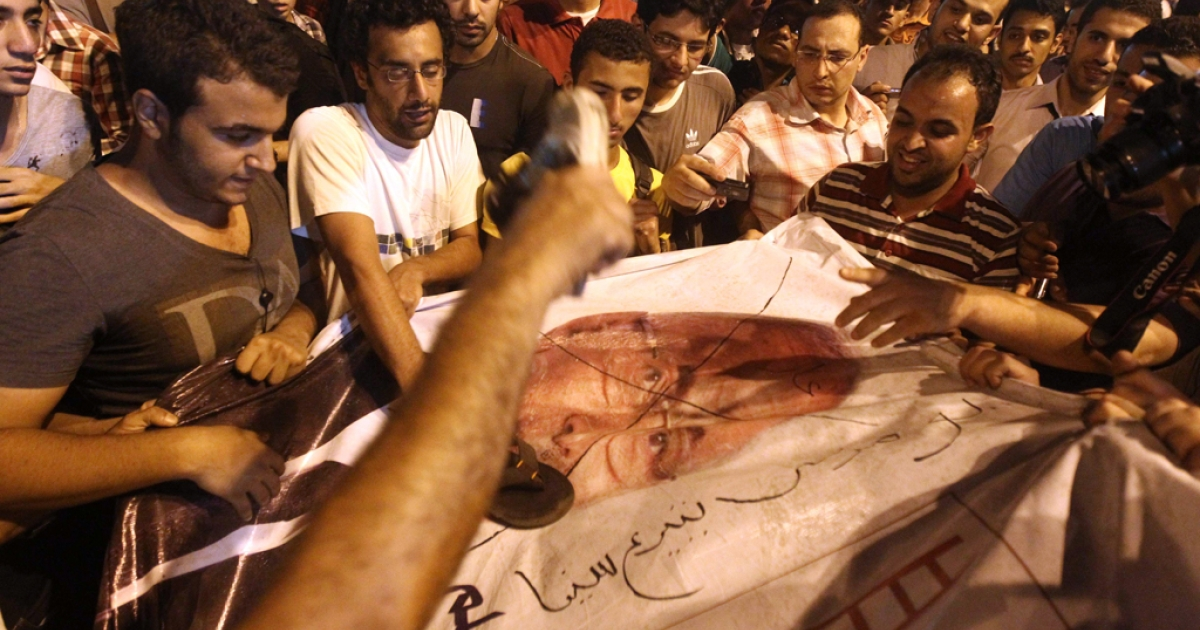 Egyptian protesters hit with shoes a portrait of presidential candidate ex-prime minister Ahmed Shafiq during a demonstration against the results of the first round of the presidential elections in Cairo on May 28, 2012.</p>
