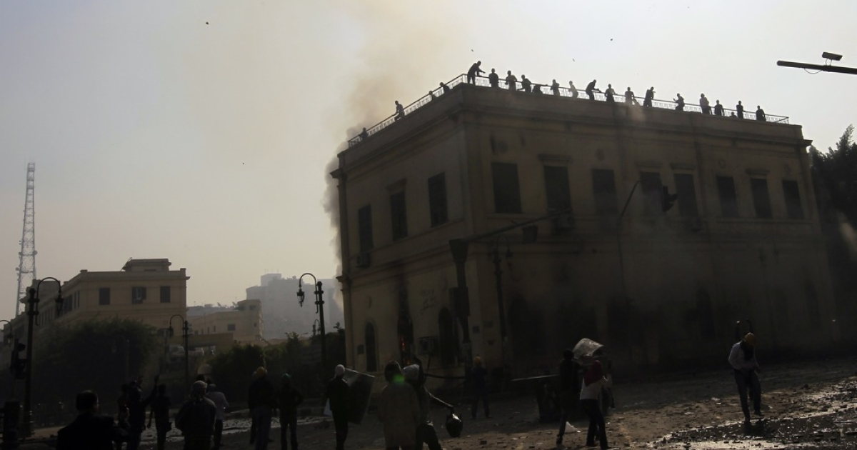 Egyptian protesters against military rule throw stones towards the Ministry of Transport and Communications during clashes in Cairo on December 17, 2011.</p>
