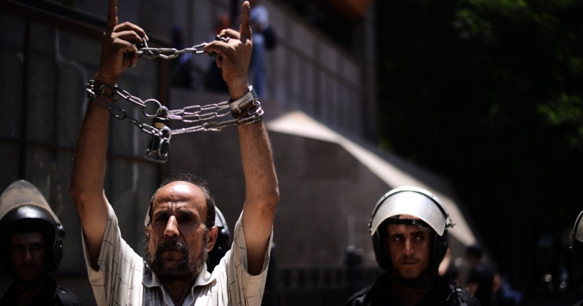 An Egyptian man who chained his wrists, protesting against military trials as demonstrators outside Cairo's administrative court await a ruling on the panel of judges designated to decide on the legitimacy of the constitutional committee, on July 30, 2012 in Cairo.</p>