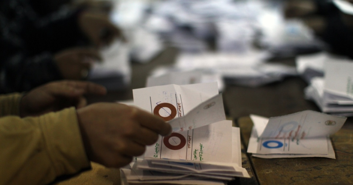 Polling station officials deposit ballots  during the second round of a referendum on a new draft constitution in Giza, south of Cairo, on December 22, 2012. Egyptians are voting in the final round of a referendum on a new constitution championed by President Mohamed Morsi and his Islamist allies against fierce protests from the secular-leaning opposition.</p>