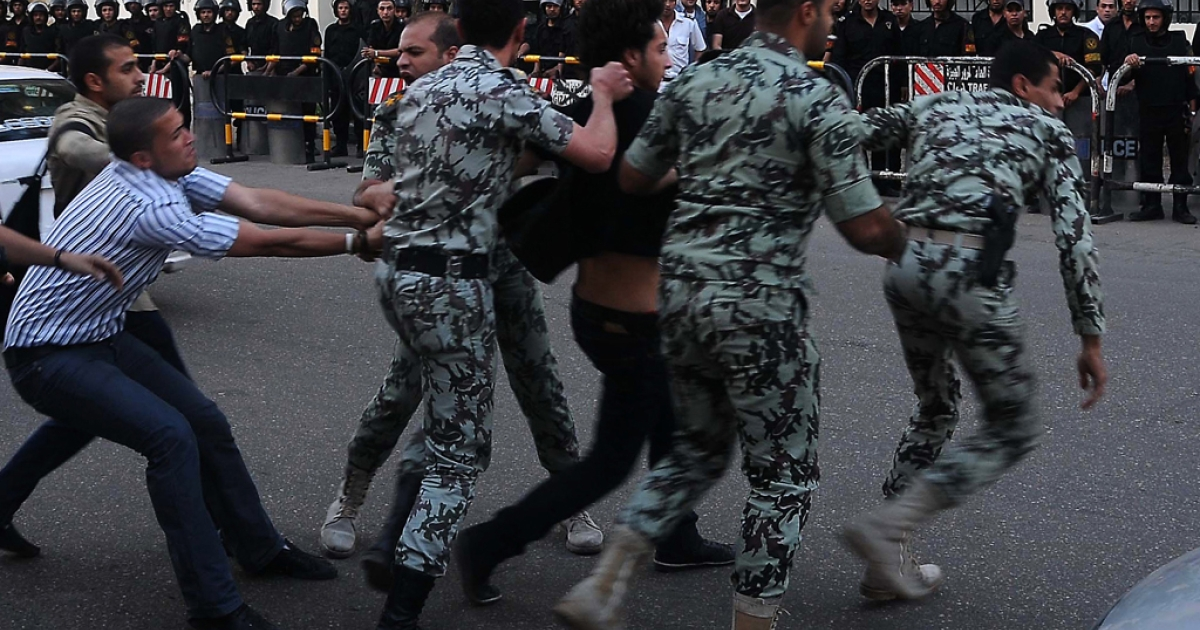 An Egyptian protester scuffles with security forces as they arrest a fellow demonstrator outside the Saudi embassy in Cairo. Egypt's administrative court on June 26, 2012, ruled against a government decree that would have allowed the military to arrest civilians.</p>