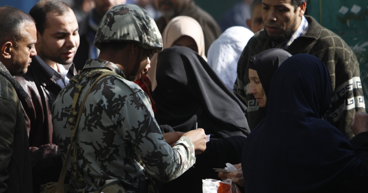 An Egyptian soldier checks the ID card of a Niqab-clad woman at the entrance of a polling station in Qaliubia, some 40 kms north of Cairo, on January 4, 2012 as Egyptians headed to the polls again in the final round of a phased election to choose the first parliament since a popular uprising toppled Hosni Mubarak in February. AFP PHOTO/MOHAMMED ABED</p>