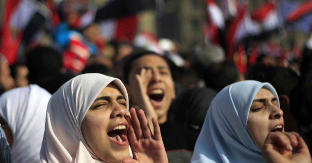 Egyptian Muslim women shout slogans as tens of thousands wave national flags during a rally on January 25, 2012 in Cairo's Tahrir Square to mark the first anniversary of the uprising that toppled Hosni Mubarak, while a debate raged over whether the rally was a celebration or a second push for change.</p>