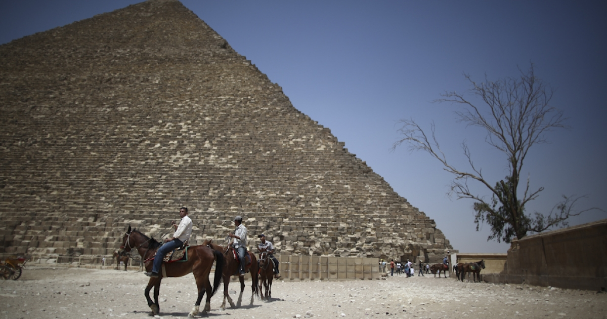 Horses for tourists pass near the Great Pyramid of Cheops in Giza, Egypt. Cheops, the largest Great Pyramid, was closed November 11, 2011 because of rumors that spiritual groups would try to hold rituals and ceremonies there, at 11:11 on 11/11/11.</p>