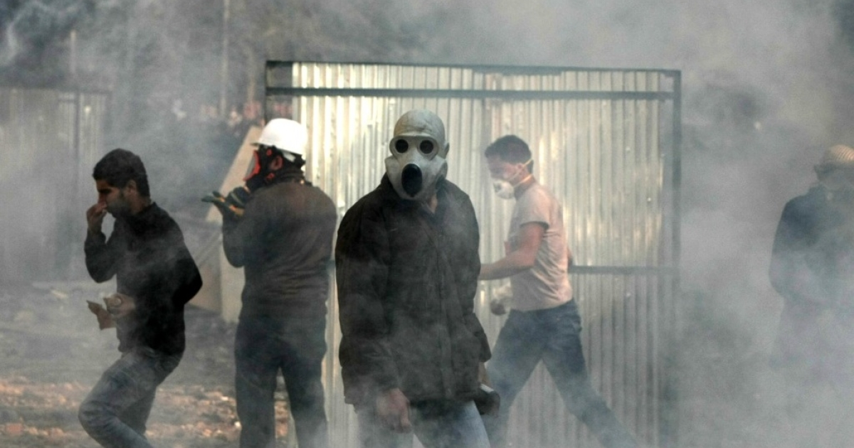 Egyptian protesters wear masks for protection against tear gas during clashes with riot police along a road which leads to the Interior Ministry, near Tahrir Square, in Cairo on November 23, 2011.</p>