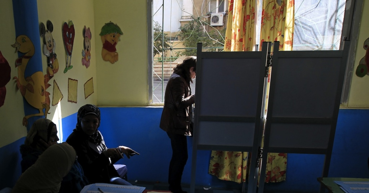 An Egyptian woman chooses her candidates in a voting booth at a polling station in Cairo's Zamalek neighbourhood on January 29, 2012 during the first stage of voting for Egypt's upper house of parliament, the Shura Council. AFP PHOTO/MAHMUD HAMS</p>
