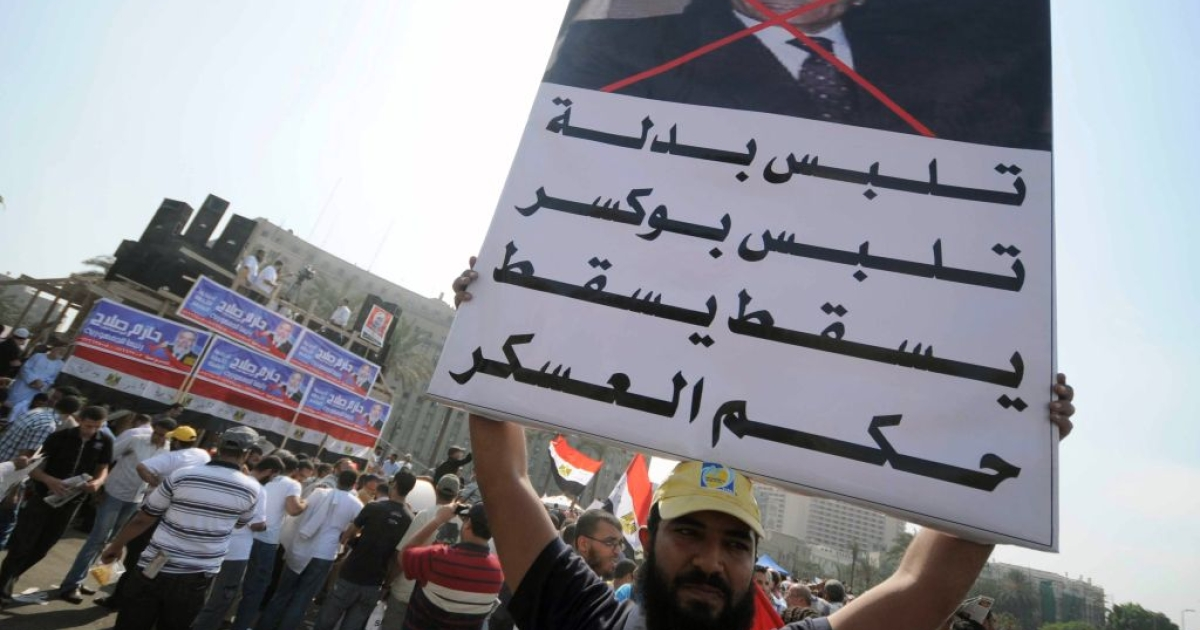 An Egyptian protester holds a banner against Field Marshal Hussein Tantawi in Cairo's Tahrir Square on September 30, 2011 during a mass rally to reclaim the revolution amid anger over the military rulers' handling of the transition.</p>