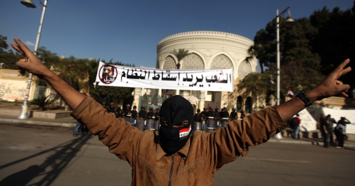 A masked supporter of the Egyptian opposition makes victory signs outside the gates of the presidential palace in Cairo on Dec. 8, 2012.</p>