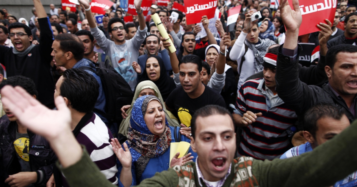 Egyptians, some holding up placards that reads in Arabic, 'No to the constitution', and some shouting slogans march to the Egyptian Presidential palace to protest against the new constitution and Egyptian President Mohamed Morsi's decree on December 4, 2012, in Cairo.</p>