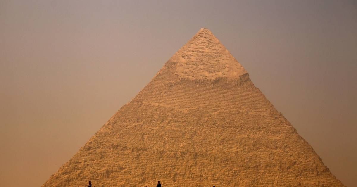 Egyptians ride their camels past the pyramid of Khafre in Giza, on the outskirts of Cairo, on November 30, 2010.</p>