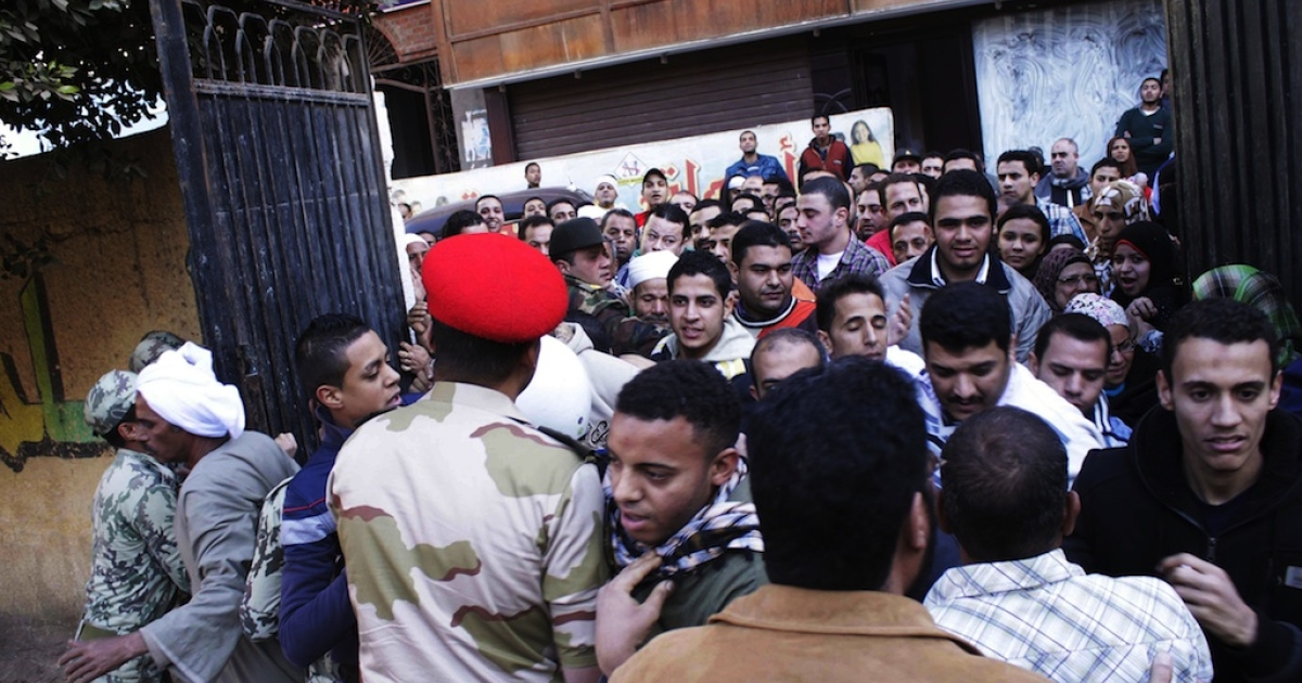 Egyptian voters scuffle with army soldiers as they enter a polling station in Giza, south of Cairo, on December 22, 2012. Egyptians voted in the final round of a referendum on a new constitution championed by President Mohamed Morsi and his Islamist allies, but with little prospect of the result quelling fierce protests.</p>