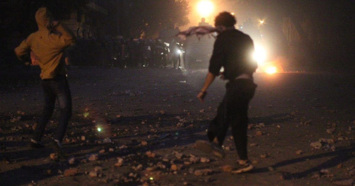 Egyptian protesters throw stones during clashes with riot police at Cairo's landmark Tahrir Square on November 19, 2011, as Egyptian police fired rubber bullets and tear gas to break up a sit-in among whose organisers were people injured during the Arab Spring which overthrew veteran president Hosni Mubarak.</p>