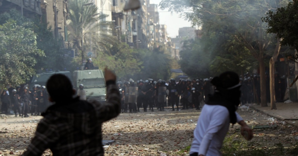 Egyptian protesters lob stones as they face off against riot police during clashes at Cairo's Tahrir Square on November 20, 2011.</p>