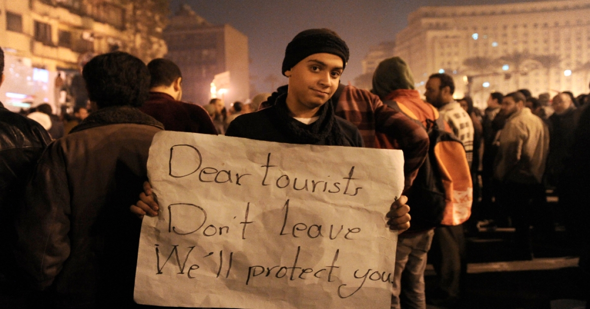 An Egyptian demonstrator demanding the ouster of Egyptian President Hosni Mubarak holds a placard asking tourists not to leave Egypt, on Cairo's Tahrir square on February 1, 2011.</p>
