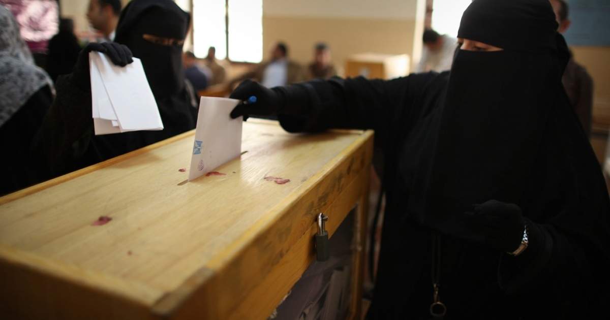 Women place their votes in a ballot box at a polling station in a girls school on November 28, 2011 in Downtown Cairo, Egypt.</p>