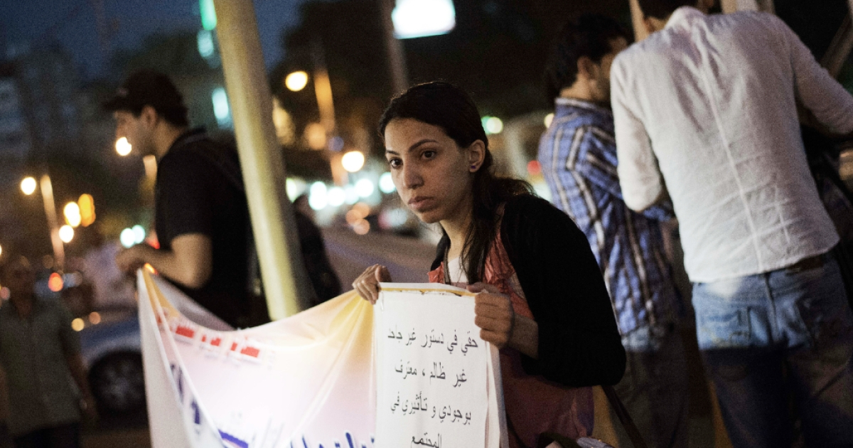 An Egyptian woman holds a slogan which reads in Arabic 'My right in the Constitution is ungrateful and unjust, I recognize my presence and effect in the community' during a demonstration in front of the presidential palace in Cairo on October 4, 2012, to support women rights in the constitution and protest against child marriage.</p>