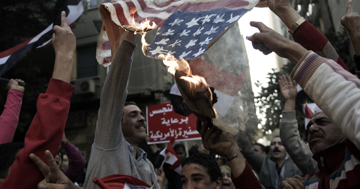 Egyptian protesters burn the US flag outside the American embassy in Cairo on March 9 before clashes broke out with security forces.</p>
