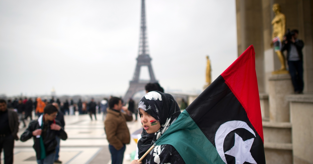 A woman holds a Libyan monarchist flag, dated from before the iron-fisted rule of Muammar Gaddafi, during a demonstration to protest against attacks by Colonel Kadhafi's planes on the people of Benghazi, on the Trocadero square in front of the Eiffel Tower, on March 19, 2011 in Paris.</p>