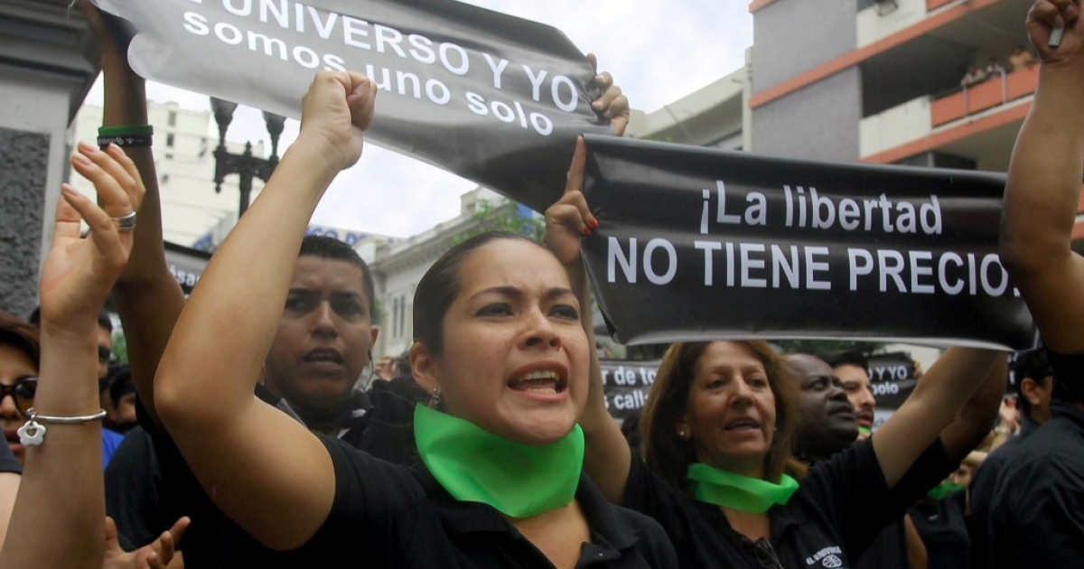 Workers of Ecuador's El Universo newspaper march in protest toward the government palace in Quito on Feb. 17. The National Court of Justice upheld a lower court ruling that sentenced the three top El Universo executives and former opinion page editor Emilio Palacio to three years in prison, and awarded Correa $40 million in damages.</p>