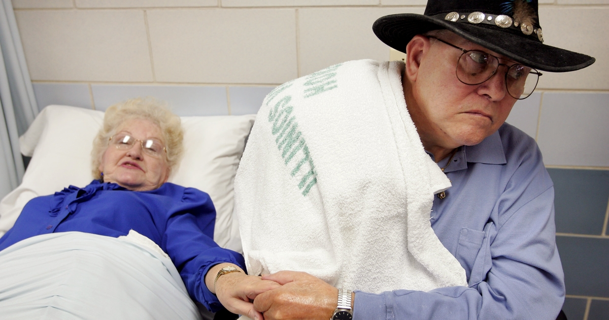 Bill Harvill, a WWII Army veteran, holds the hand of his wife Rose as they undergo physical therapy at the Quincy Veterans Home in Quincy, Ill., on Feb. 17, 2005.</p>