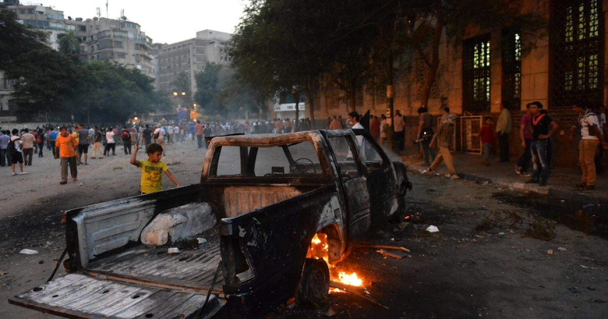 A burnt pick-up truck is seen during clashes between Egyptian protesters and riot police near the US embassy in Cairo on Sept. 13, 2012. Protests have erupted since Sept. 11 outside US diplomatic missions in several Arab and Muslim states by demonstrators who deem the low-budget movie 'Innocence of Muslims' made in the United States as offensive to Islam.</p>
