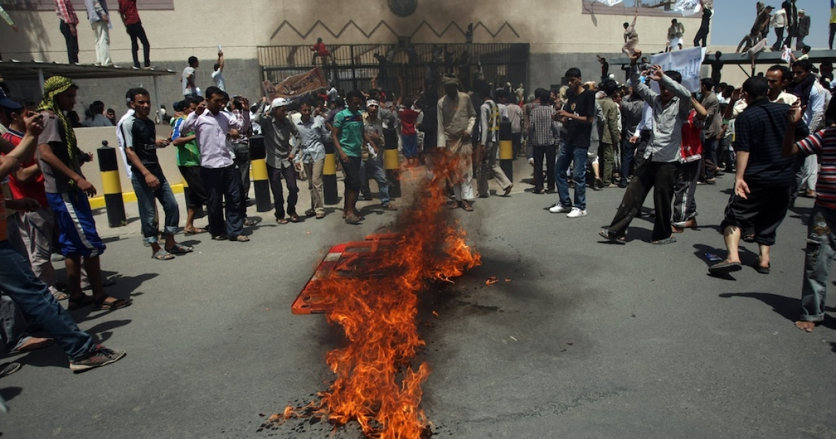 Yemeni protesters gather around fire during a demonstration outside the US Embassy in Sanaa over a film mocking Islam, on Sept. 13, 2012. Yemeni forces managed to drive out angry protesters who stormed the embassy in the capital, with police firing warning shots to disperse thousands of people as they approached the main gate of the mission.</p>
