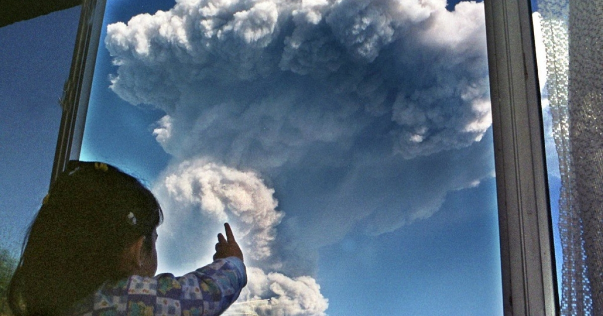 A little girl watches a mushroom-shaped cloud forming in the sky as the nearby Guagua Pichincha volcano near Quito, Ecuador, spouts boiling water and ash. Perhaps she's wondering if the end of the world is near?</p>