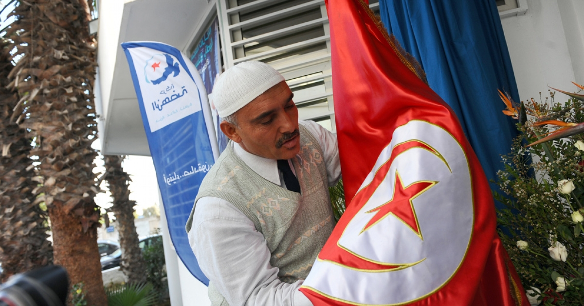 A supporter of Tunisia's Islamist Ennahda party touches the national flag on October 26, 2011 at the movement headquarters in Tunis.</p>