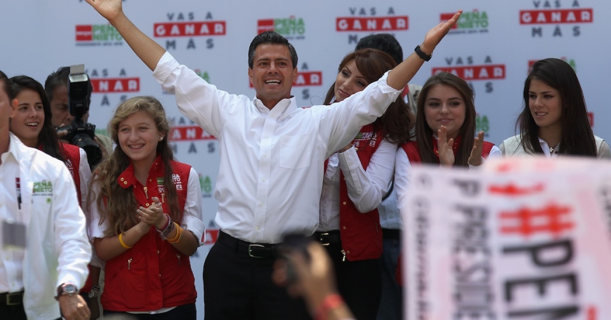 Front-runner Enrique Pena Nieto stands with his family while greeting supporters at his final campaign rally on June 24, 2012 in Mexico City.</p>