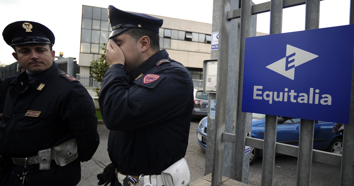 Police officers stand outside the gate of Italian tax collection agency Equitalia after a letter bomb exploded in its central office in Rome, injuring director Marco Cuccagna.</p>
