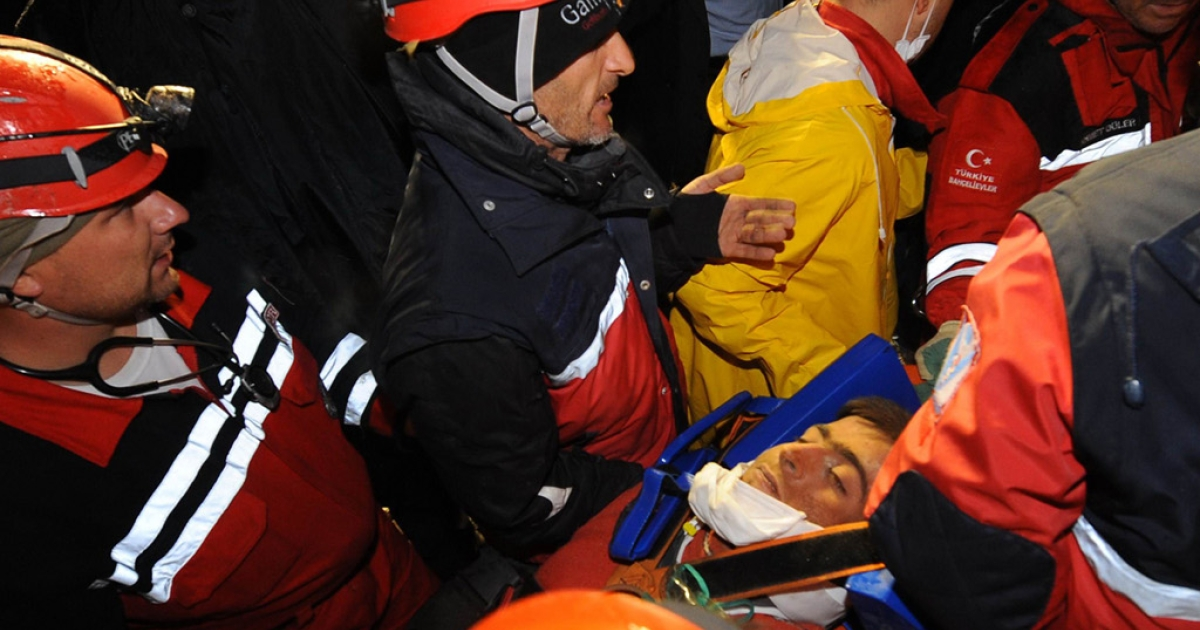 Aydin Palak, 18, is pulled out by Turkish rescuers from the rubble of a collapsed bulding in Ercis on October 27, 2011.</p>