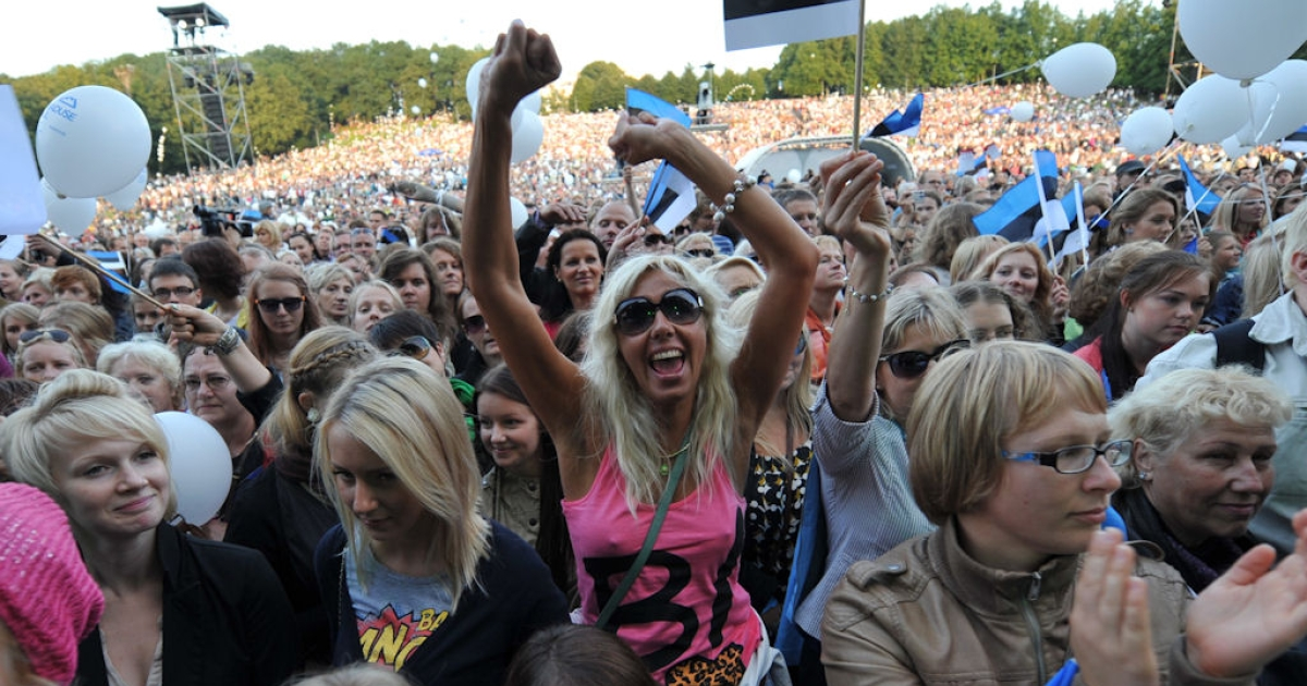 People wave Estonian flags as they attend the concert