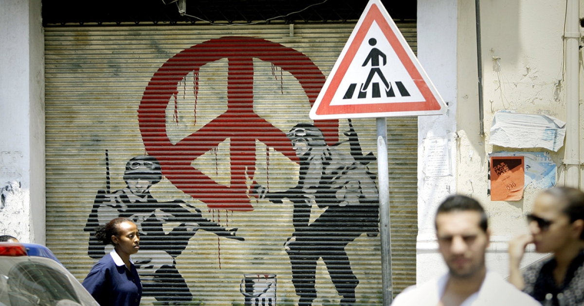 An Ethiopian woman walks past a shuttered shop decorated with images of two solider and the 'Love and Peace' sign in the Christian neighbourhood of Jemmayzeh in Beirut on July 11, 2012.</p>