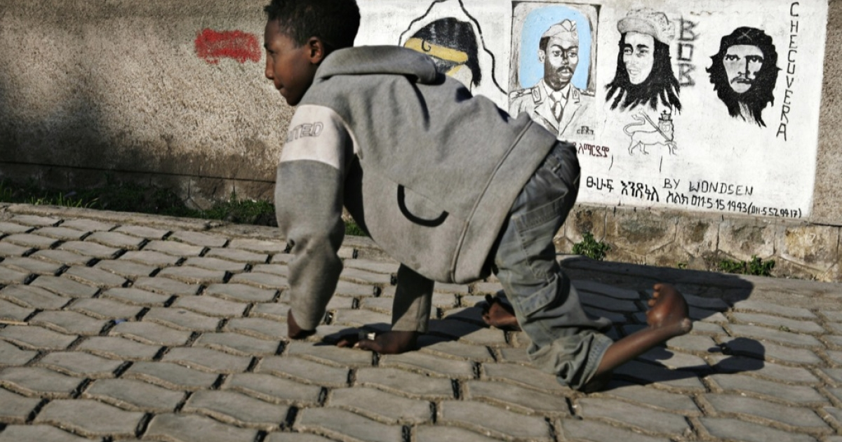 A disabled boy walks past a mural showing Argentinian revolutionary Che Guevara (L), Jamaican singer Bob Marley (C) and Ethiopian dictator Mengistu Haile Mariam (R) Oct. 6, 2007 in Addis Ababa, Ethiopia.</p>