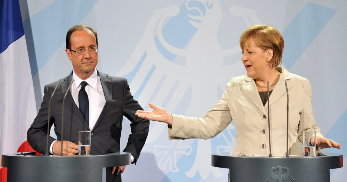 German chancellor Angela Merkel (R) speaks next to the French president Francois Hollande (L) during a joint press conference at the German Chancellery.</p>