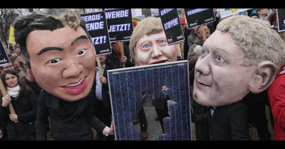 Puppets of German Vice Chancellor and Economy Minister Philipp Roesler (left), Chancellor Angela Merkel and Environment Minister Norbert Roettgen pose with a broken solar panel.</p>