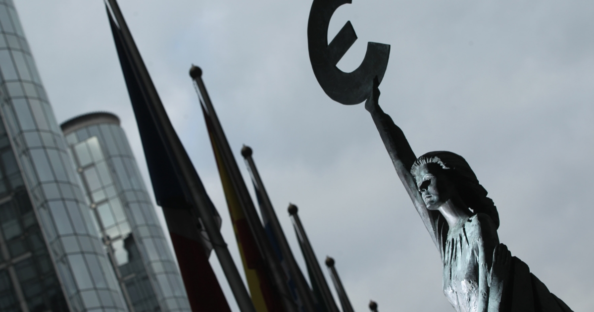 The 'Europe' sculpture of Belgian artist May Claerhout showing a woman holding up the symbol of the Euro stands outside the European Parliament building on November 17, 2011 in Brussels, Belgium.</p>
