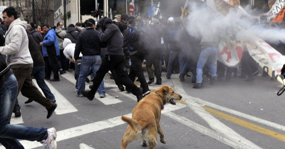Protesters run from tear gas during clashes which broke out at a march in Athens on Feb. 23, 2011. Greece was hit with a general strike against government austerity measures as Prime Minister George Papandreou seeks to convince the cash-strapped country's euro zone partners to extend the repayment of a massive rescue loan.</p>