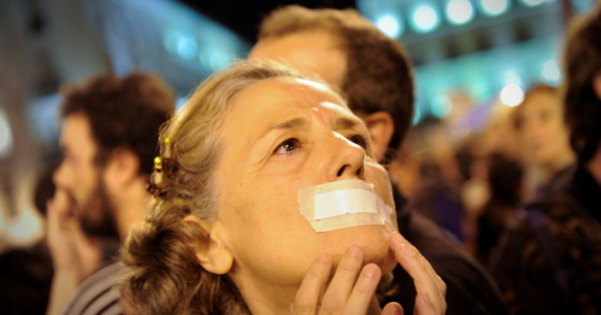 A woman with her mouth taped shut participates in a protest against Spain's economic crisis and its sky-high jobless rate at the Puerta del Sol square in Madrid on May 20, 2011.</p>