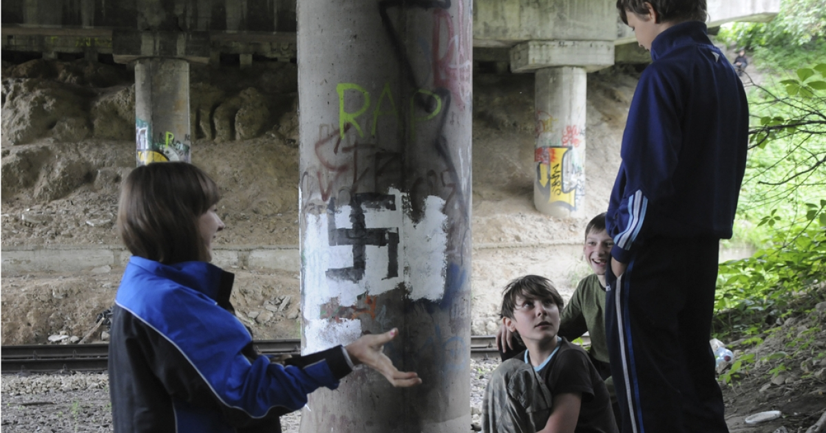 Children play near a bridge column with Nazi graffiti in Lviv, Ukraine, on May 30, 2012. Euro 2012 organizers refute claims that Poland and Ukraine were unsafe for traveling soccer fans.</p>