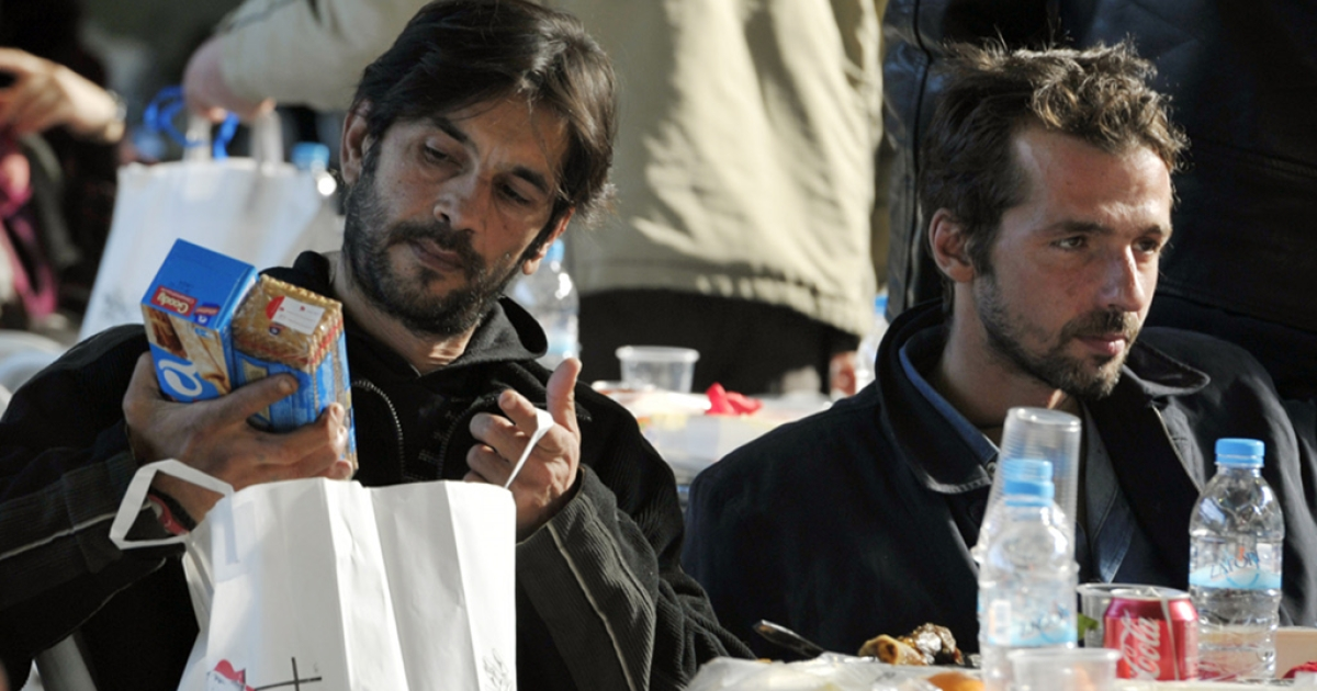 Homeless men in Athens greet the new year by opening food parcels donated by the city government</p>