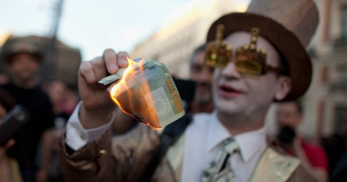 A demonstrator with Spain's Indignant movement dressed as a banker burns a euro note during a rally at Puerta del Sol on May 15, 2012 in Madrid, Spain. The European Commission recommended leeway for Spain and its troubled banking sector, but Germany is unlikely to give the nod.</p>
