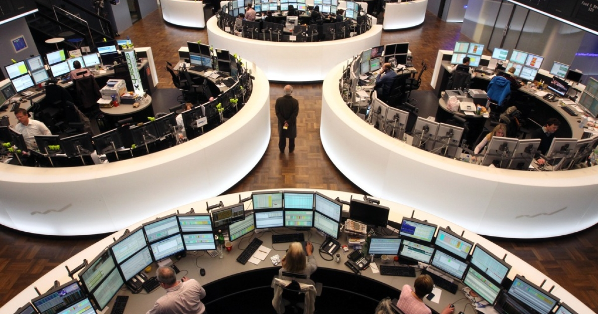 Brokers sit in front of screens showing the German market rates at the German stock exchange in Frankfurt/Main, on March 9, 2012.</p>