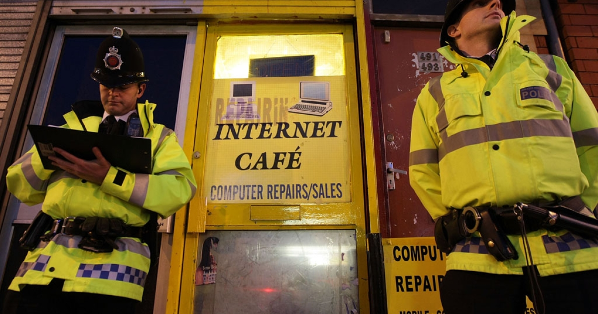 Police officers guard an internet cafe in Manchester, England, after anti-terror raids on April 8, 2009.</p>