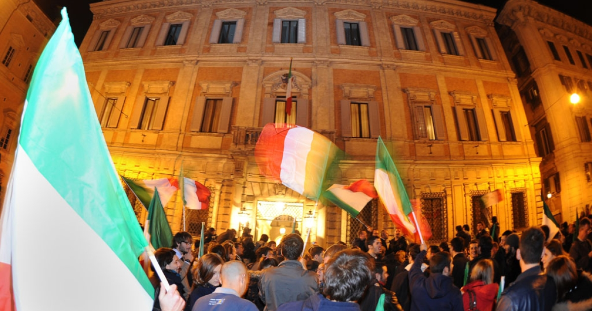 Italian Prime Minister Silvio Berlusconi's supporters wave Italian flags in front of his residence, Palazzo Grazzioli, the day after he resigned on Nov. 13, 2011 in Rome.</p>